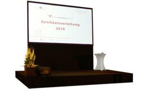 Bühne mit schwarzem Teppich und dahinter einer Leinwand und Konferenztechnik in Wien