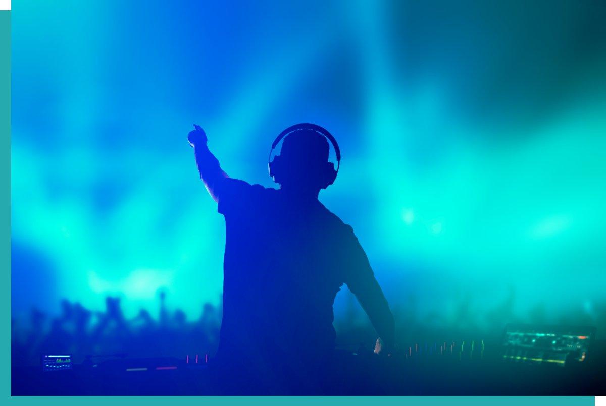 DJ mit Equipment vor tanzendem Publikum mit grüner und blauer Lichttechnik