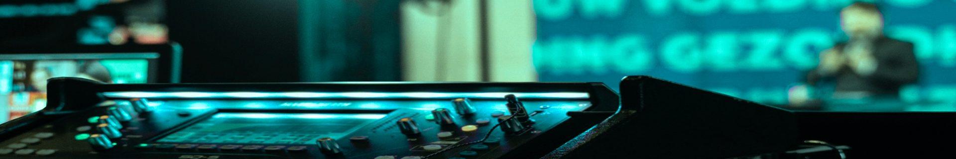 Mischpult im Vordergrund mit Sprecher im Hintergrund bei online-Veranstaltung
